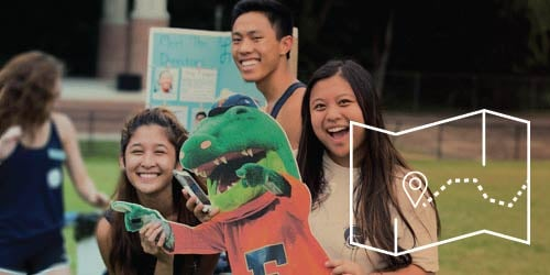 Three international students holding up a paper cut out of the UF mascot
